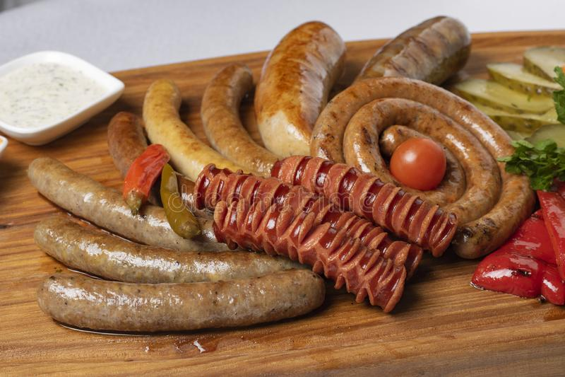 Pepinos conservados, salsichas fervidas, queijo com tomates fritados, salsa e cereja no restaurante foto de stock