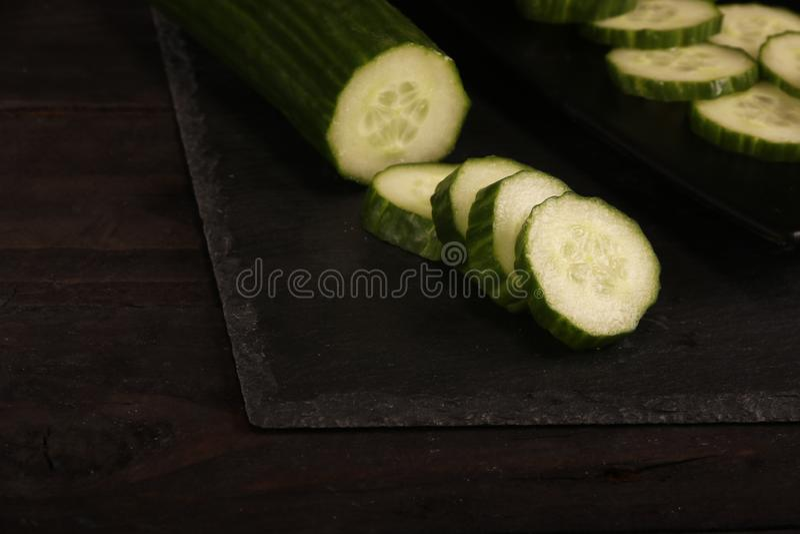 Pepinos cortados frescos na placa de corte preta e no fundo rústico de madeira Teste padrão colocado liso de pepinos verdes na ta fotografia de stock