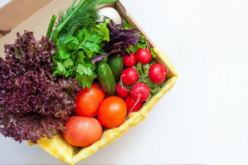 Pepinos frescos, tomates, rábanos, lechuga, albahaca, perejil en una caja con una servilleta amarilla Espacio para el texto fotos de archivo