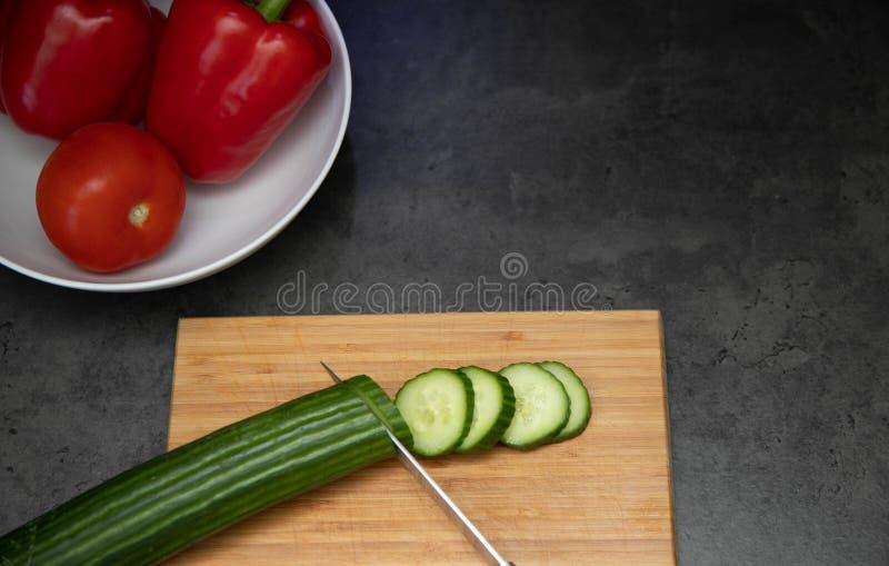 Pepinos recientemente cortados con el cuchillo en tabla de cortar de madera con una placa de la paprika y del tomate foto de archivo