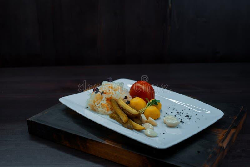 Pepinos salgados com tomates e o chucrute vermelhos com cravos-da-índia de alho em uma tabela de madeira em um restaurante foto de stock
