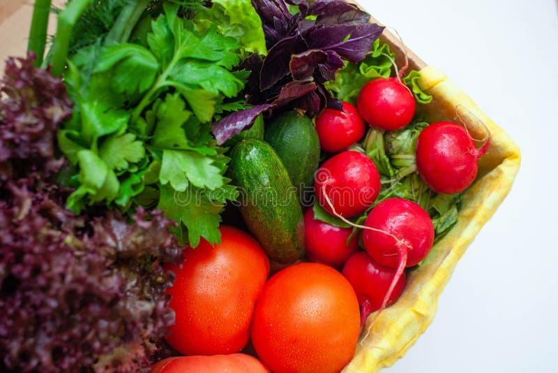 Pepinos, tomates, rábanos, lechuga, albahaca, perejil en una caja con una servilleta amarilla Espacio para el texto fotos de archivo libres de regalías