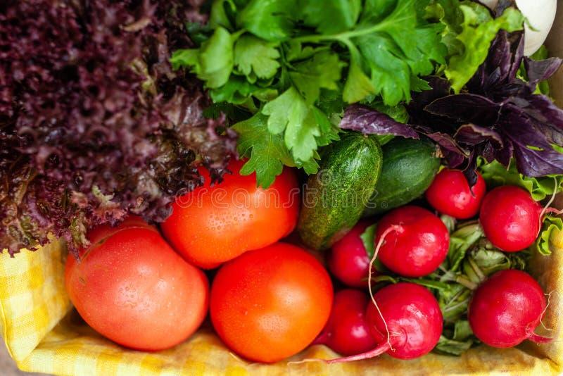 Pepinos, tomates, rábanos, lechuga, albahaca, perejil en una caja con una servilleta amarilla Visi?n superior fotos de archivo libres de regalías