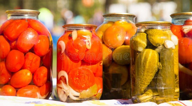 Pepinos y tomates conservados en los tarros de cristal foto de archivo libre de regalías