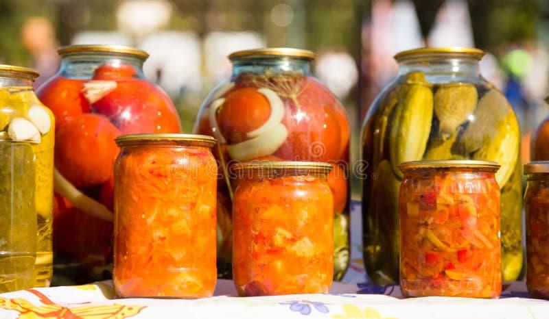 Pepinos y tomates conservados en los tarros de cristal imagen de archivo libre de regalías
