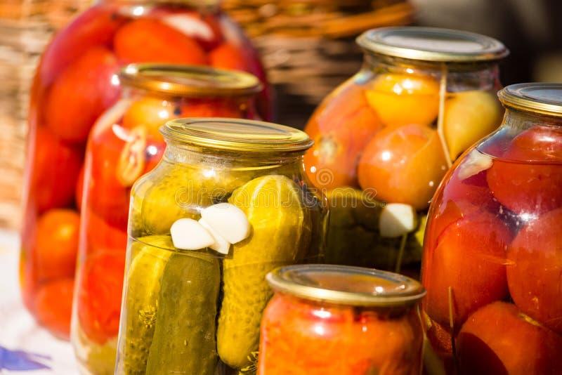 Pepinos y tomates conservados en los tarros de cristal fotografía de archivo