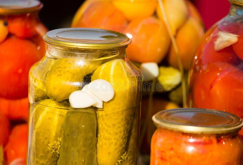 Pepinos y tomates conservados en los tarros de cristal fotografía de archivo libre de regalías