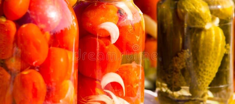 Pepinos y tomates conservados en los tarros de cristal imagen de archivo