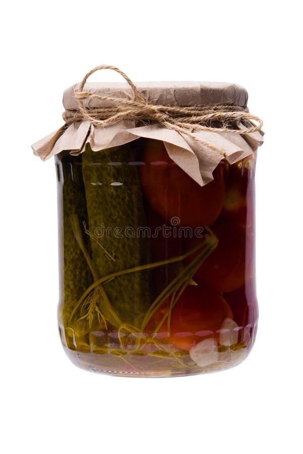 Pepinos y tomates salados, en un tarro de cristal cerrado con una tapa fotografía de archivo