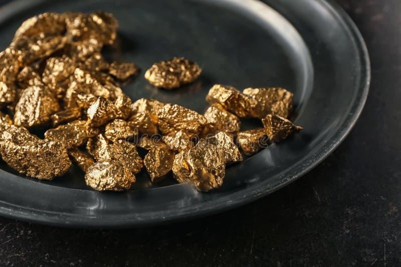 Pepitas de oro en la placa de metal, primer fotografía de archivo