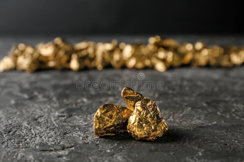 Pepitas de oro en la tabla oscura fotos de archivo