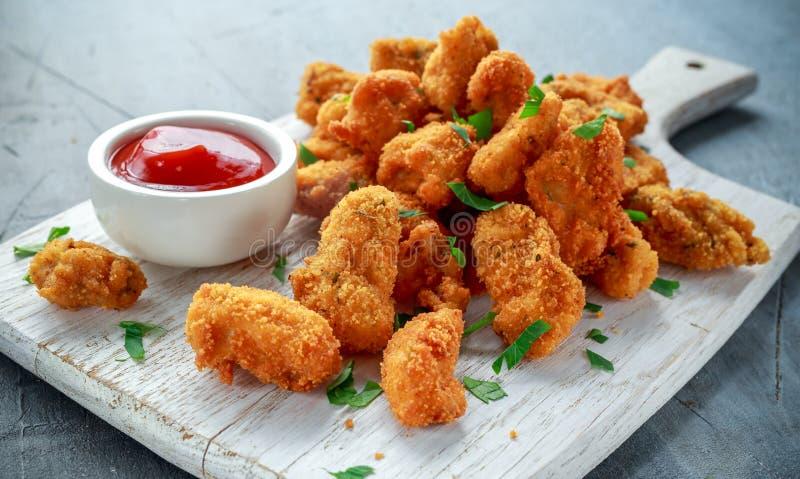 Pepitas de pollo curruscantes fritas con la salsa de tomate en el tablero blanco foto de archivo libre de regalías