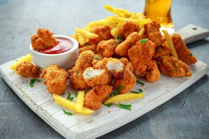 Pepitas de pollo curruscantes fritas con las patatas fritas, la salsa de tomate y la cerveza en el tablero blanco fotos de archivo