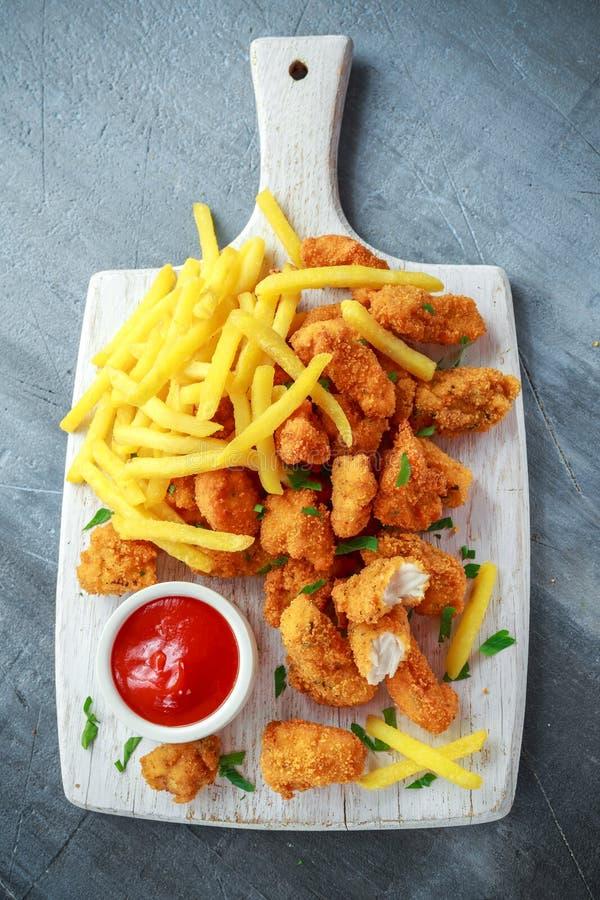Pepitas de pollo curruscantes fritas con las patatas fritas y la salsa de tomate en el tablero blanco fotos de archivo