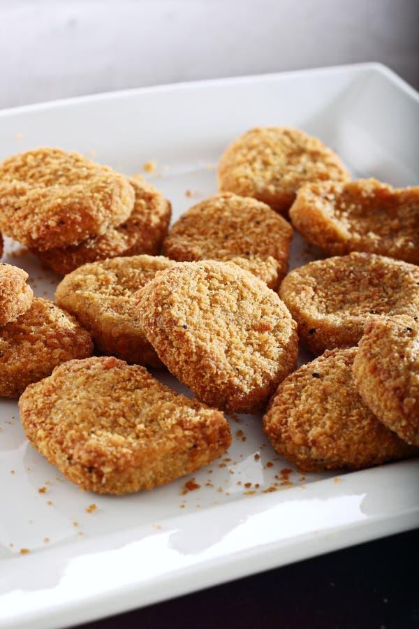 Pepitas de pollo empanadas en una placa. imagen de archivo