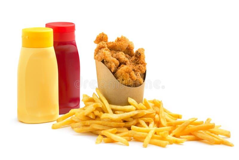 Pepitas de pollo, fritadas y condimentos foto de archivo