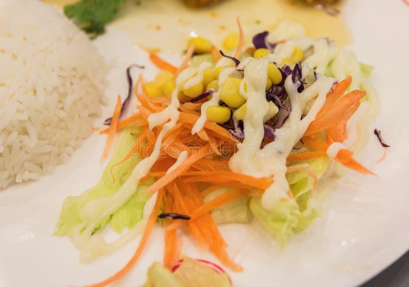 Pepitas de pollo y ensalada vegetal en una placa blanca fotos de archivo