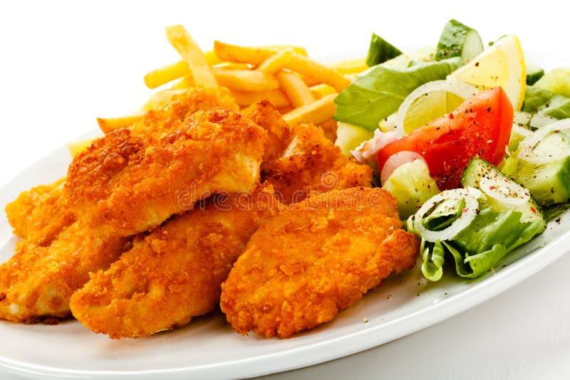 Pepitas e vegetais de galinha fritada foto de stock