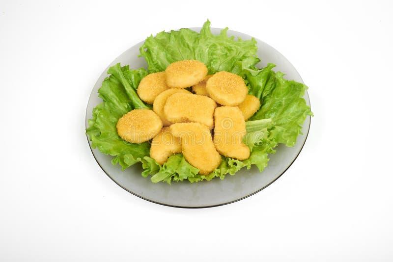 Pepitas y verduras de pollo en una placa blanca, aislada en blanco imagen de archivo