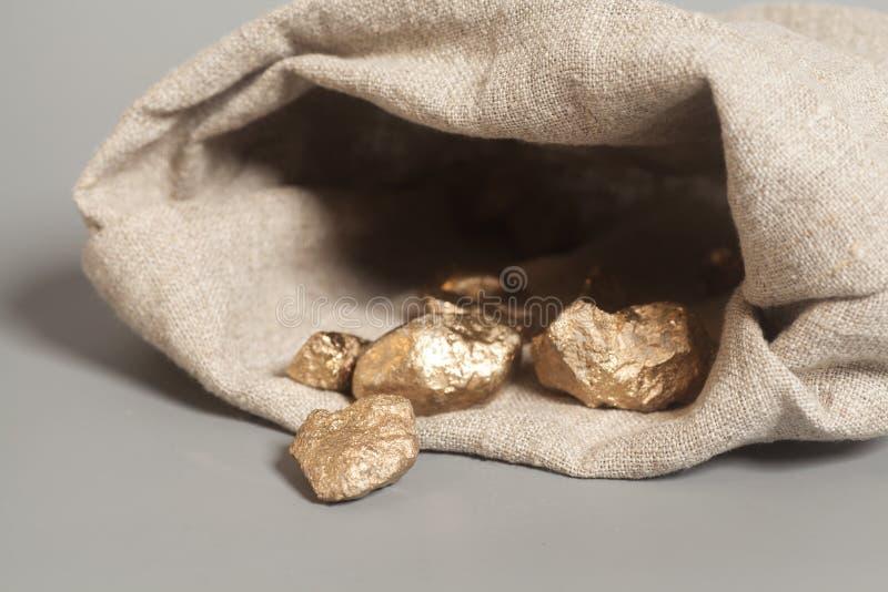 Pepite di oro che si rovesciano fuori dal sacchetto fotografia stock