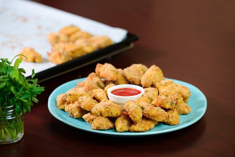 Pepite di pollo croccanti fritte con ketchup sul piatto immagini stock libere da diritti
