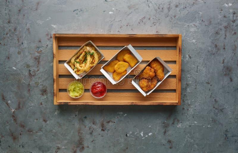 Pepite di pollo fritto con le gambe ed il polipo croccante sul vassoio di legno, vista superiore, spazio della copia Concetto del immagini stock libere da diritti