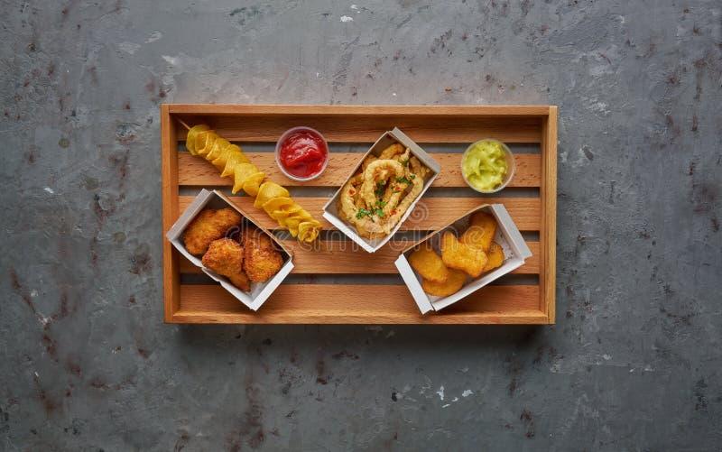 Pepite di pollo fritto, gambe, polipo croccante e patatine fritte a spirale sul vassoio di legno, vista superiore, spazio della c immagini stock