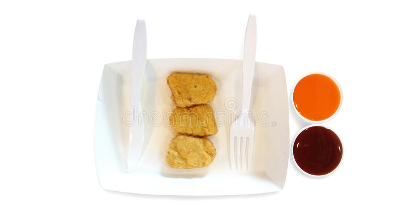 Pepite di pollo fritto sul piatto di carta con l'isolante dolce della salsa di peperoncino rosso fotografia stock libera da diritti