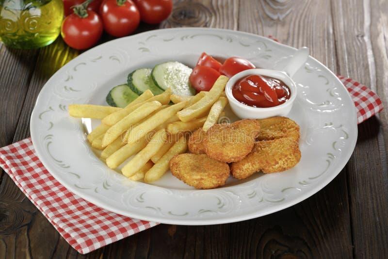 Pepite di pollo, patate fritte e verdure in piatto bianco sulla tavola di legno fotografie stock