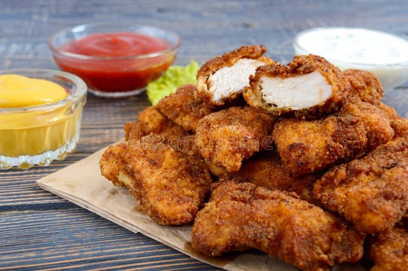 Pepite di pollo Pezzi di carne croccante fritta in grasso bollente, su carta con differenti salse su una tavola di legno fotografia stock