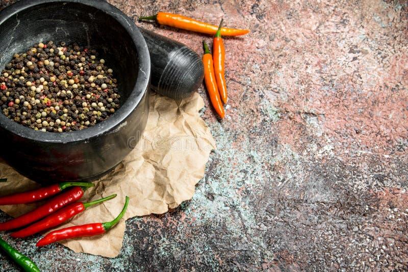 Pepparärtor i en mortel och en mortelstöt arkivbilder