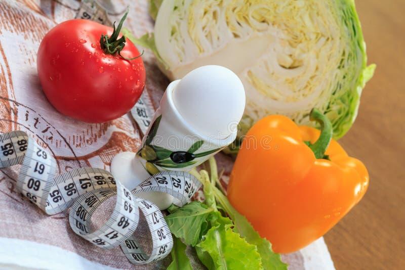 Peppar, ägg, kål, tomat, sallad och linjal på tabellen arkivbilder