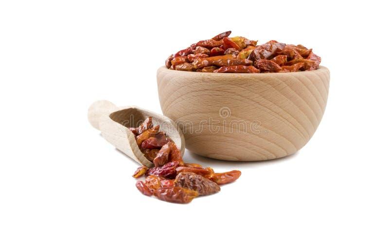 Peppar för chilipeperoncinipaprika i träbunke och skopan som isoleras på vit bakgrund Kryddor och matingredienser royaltyfri bild