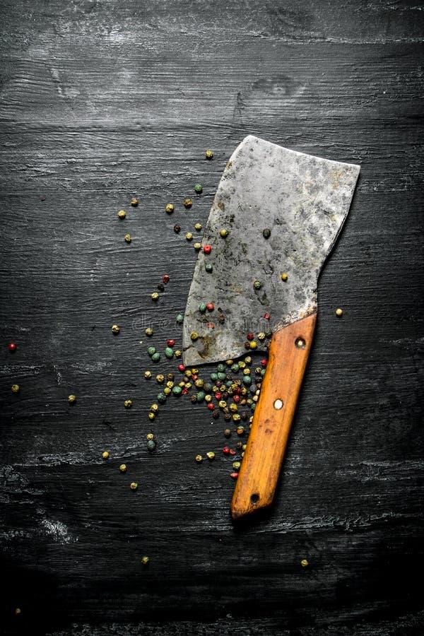 Peppar, kryddor och en gammal handyxa På svart lantlig bakgrund arkivfoto