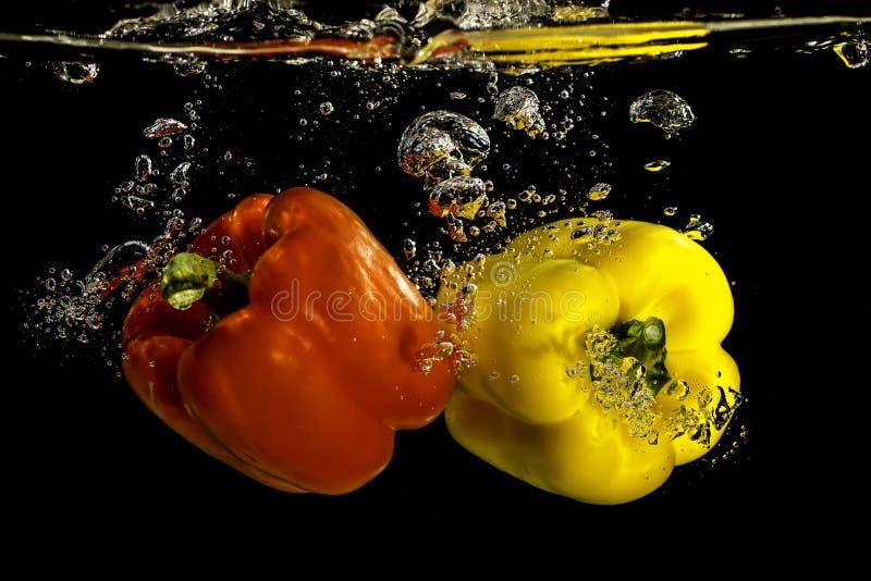 Peppar som faller in i vatten fotografering för bildbyråer