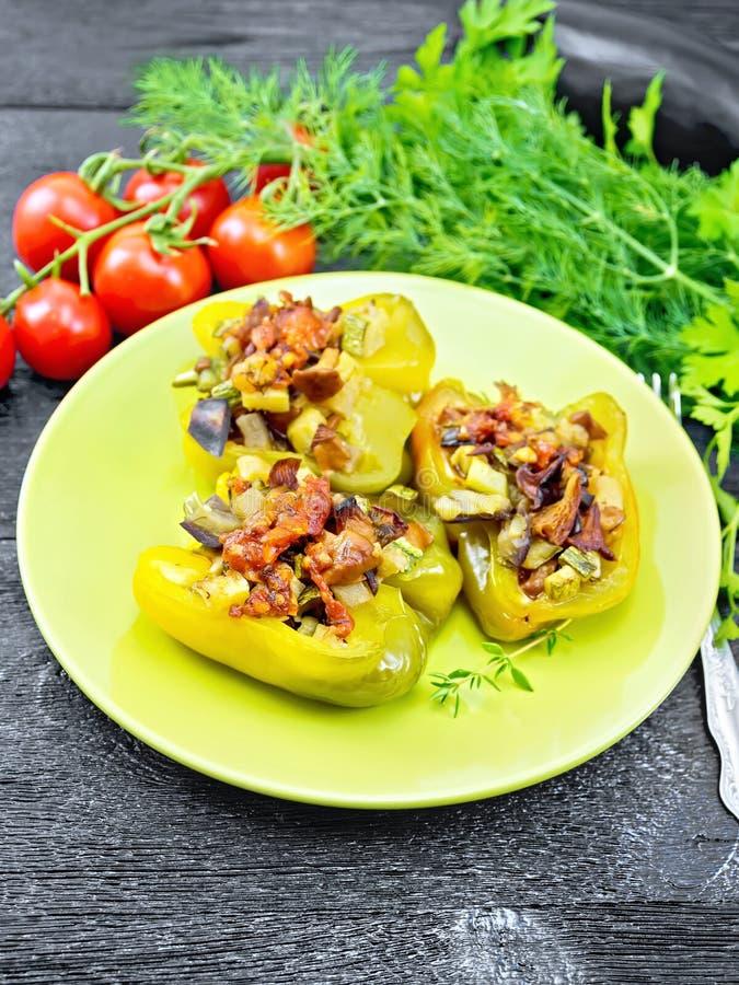 Peppar som stoppas med grönsaker i grön platta på träbräde fotografering för bildbyråer