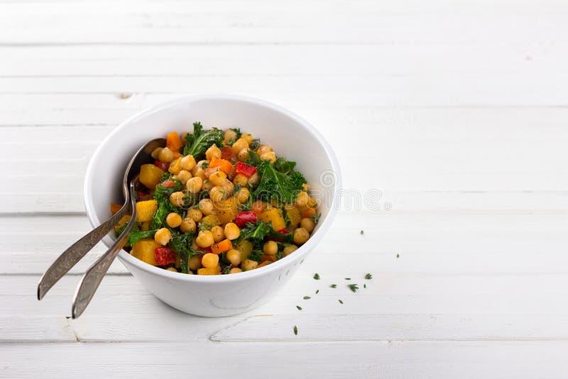 Peppar-, tomat-, kikärt-, grönkål- och timjanragu med pumpa, morötter, söta peppar, tomater arkivfoto