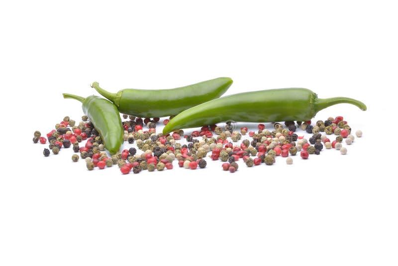 Pepparen och pepparkryddan på vit bakgrund arkivfoton