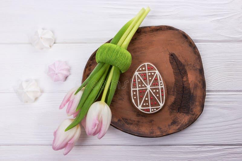 Pepparkaka för påskägg, keramisk platta, marängar och rosa färgtulpan på träbakgrund arkivbild