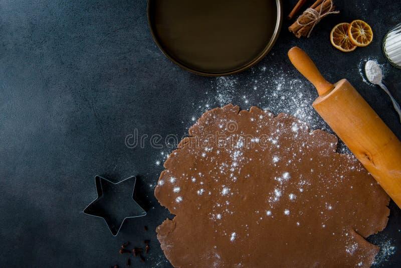 Pepparkakadeg med mjöl och kavlen på mörk bakgrund royaltyfri fotografi