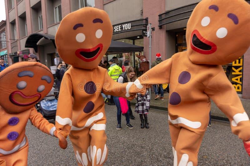 Pepparkakadräktfolk som in dansar och agerar på en stadsgata, under Yaletown CandyTown arkivbild