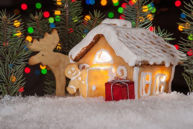 Pepparkakahus med pepparkakamannen, älgen och julträd royaltyfri fotografi