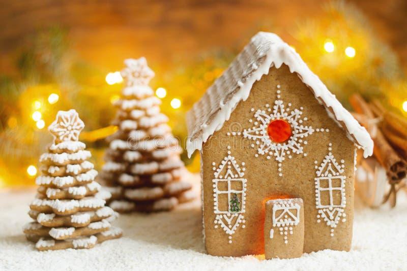 Pepparkakahus och julgranar på en lysande bakgrund Bokeh verkställer arkivfoto