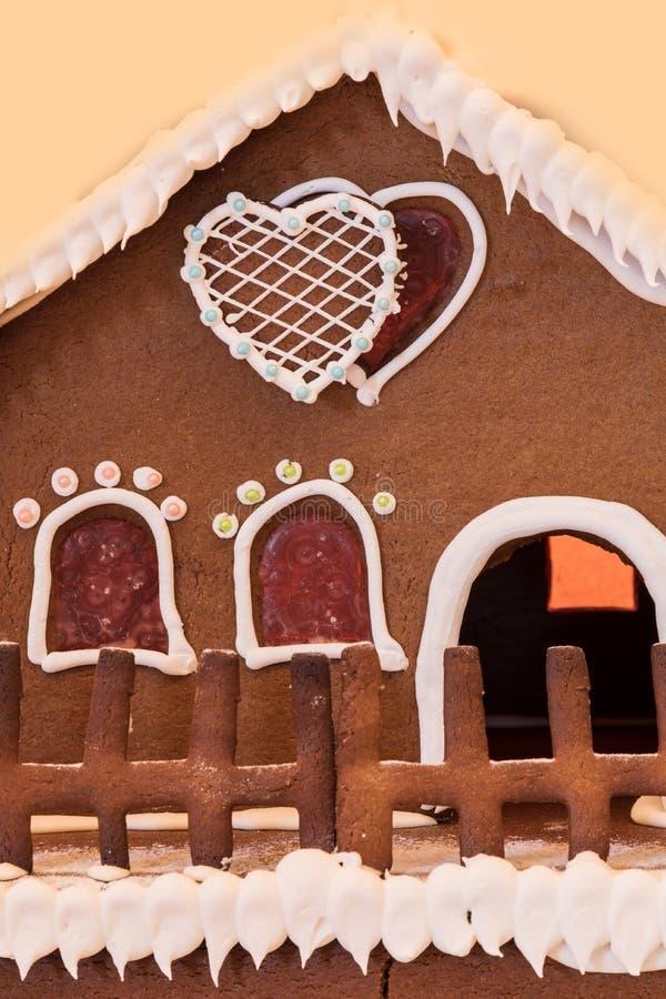 Pepparkakahuset med vit isläggning och hjärta formade fönster med royaltyfria foton