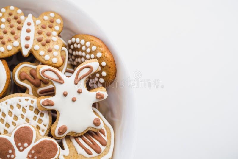 Pepparkakakakor i formen av påskkaninen, hjärta, fjärilen och blommor som täckas med vit- och chokladflorsocker arkivfoton
