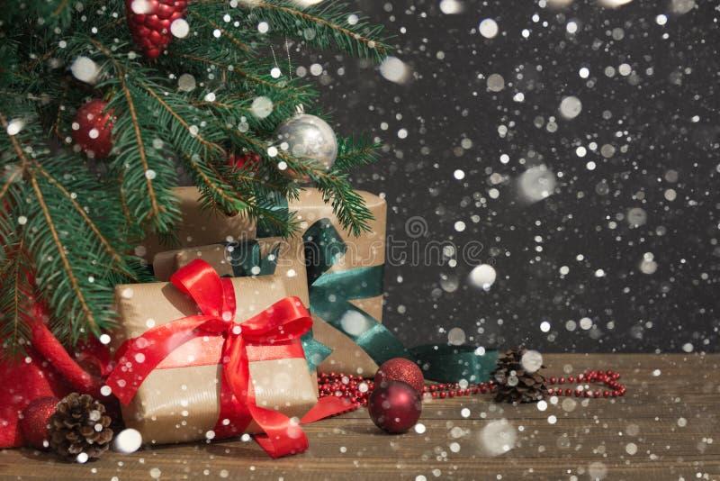 Pepparkakaman över trä Gåvor med en röd band-, för jultomten` s hatt och dekoren under en julgran på ett träbräde arkivfoton