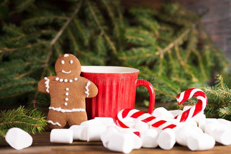 Pepparkakaman nära den stor röd koppen och julgran, jul rotting och marshmallow royaltyfria foton