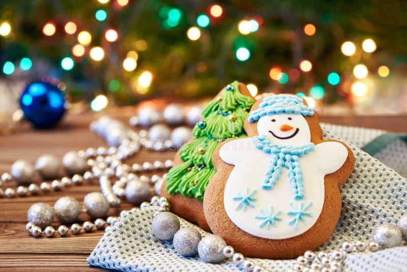Pepparkakor snögubbe och dekorerat julträd fotografering för bildbyråer