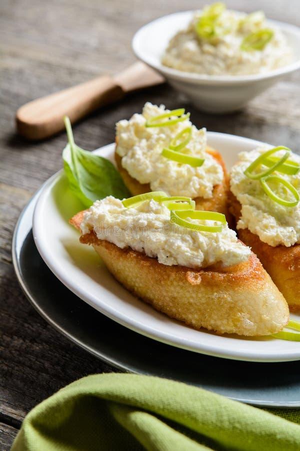 Pepparrot och ostmassa fördelade på den stekte äggbagetten arkivbild