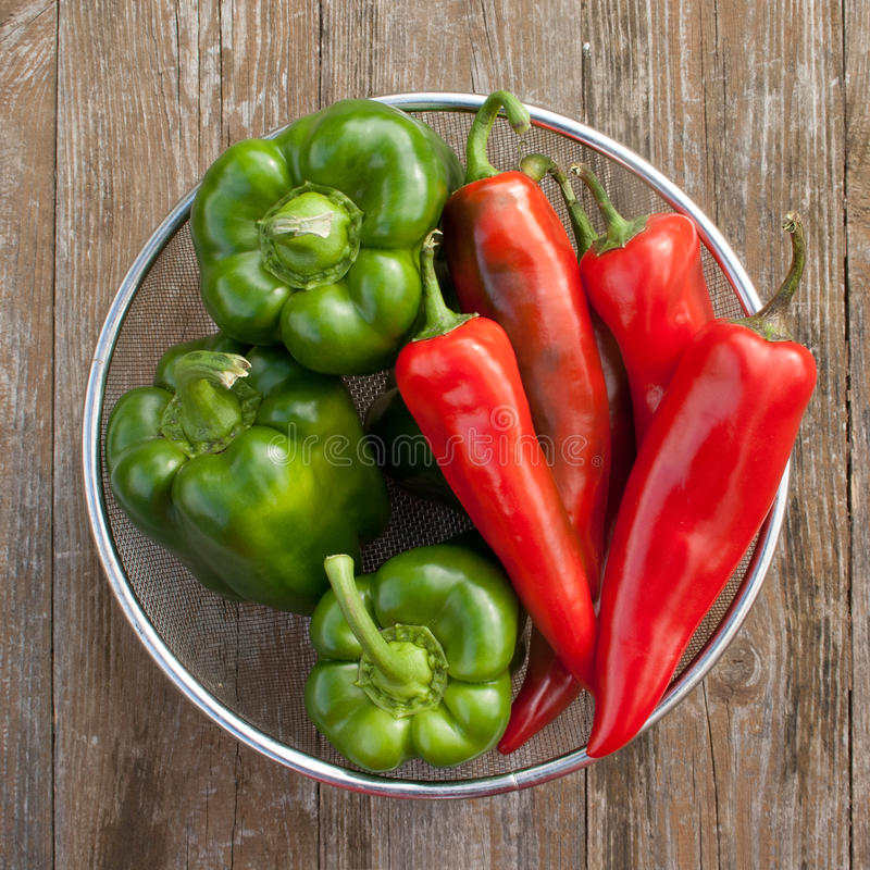 Pepper. Bowl with red and green pepper on wooden table stock image